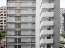コンクリート打放しの外観に金属性の横格子手摺が際立つ、シャープな印象の賃貸マンション