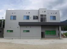 山上のプラント工場と離れた場所に位置する事務所を平地に移設、一体化することで不便さを解消。利用者に優しい設置の建築